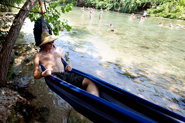 <p>Michael Plemons relaxes in his hammock at the Barton Springs Spillway Thursday afternoon. Plemons said it's a good way to beat the heat because hammocks are always attached to trees and in the shade.</p>