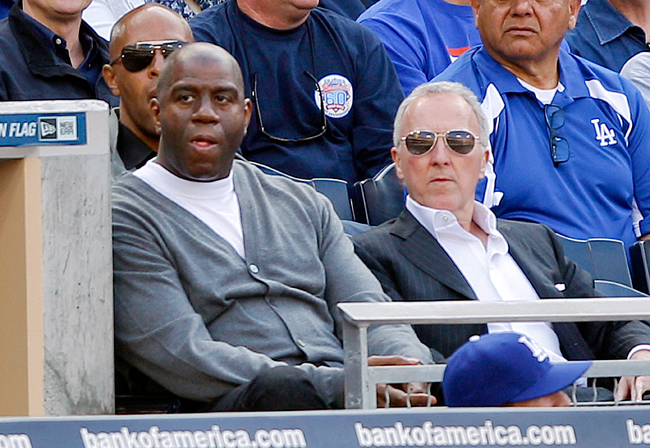 <p>Former Lakers star Magic Johnson, left, and Los Angeles Dodgers owner Frank McCourt watch the Dodgers play the against the San Diego Padres on opening day for the two baseball teams in early April. Ever since ownership traded hands, the Dodgers have played exceptionally well.</p>