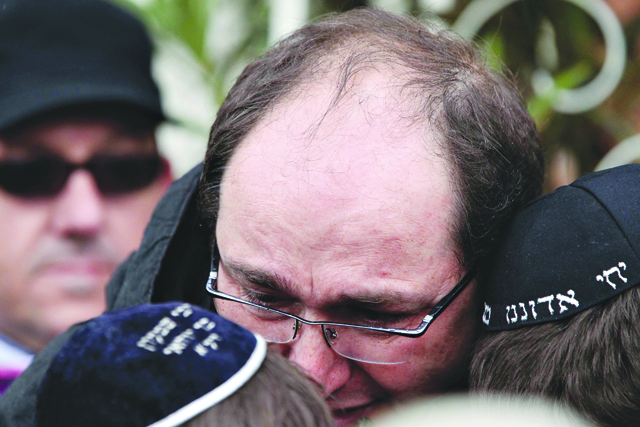 <p>An unidentified man comforts schoolchildren as they leave their Jewish private school after a gunman opened fire killing several people in Toulouse, southwestern France, Monday, March 19, 2012. A father and his two sons were among four people who died Monday when a gunman opened fire in front of a Jewish school, the Toulouse prosecutor said Monday.</p>