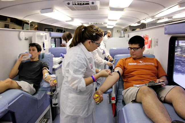 <p>Freshmen Stephen Armstrong and Sergio Rodriguez participate in the blood drive hosted by the Ahmadiyya Muslim Student Organization on Speedway Street Monday afternoon. </p>