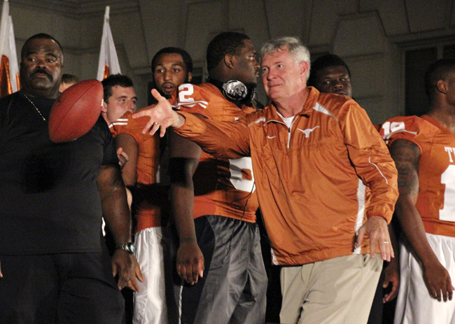 <p>Mack Brown, head coach of the Texas Longhorn football team, tosses the official game ball to a member of the Navy ROTC at Wednesday night's torchlight rally. As is tradition, the Texas Navy ROTC will then carry the ball 200 miles to Dallas, where they will then play the OU Navy ROTC team in their annual football game.</p>