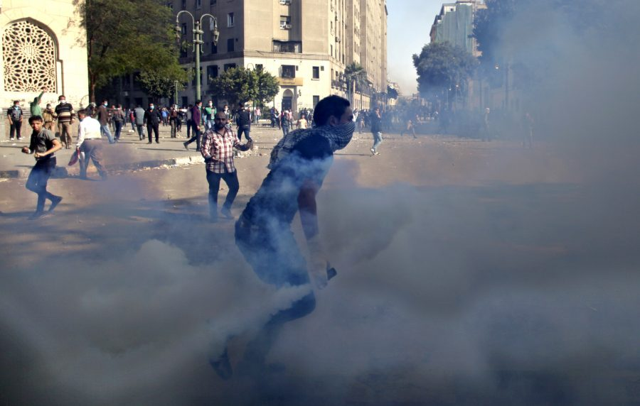 <p>Egyptian protesters clash with security forces near Tahrir square, in Cairo, Egypt, Wednesday, Nov. 28, 2012. Egyptian state television says the country's highest appeal court has decided to suspend its work nationwide to protest the president's decrees giving himself nearly absolute powers. (AP Photo/ Khalil Hamra)</p>