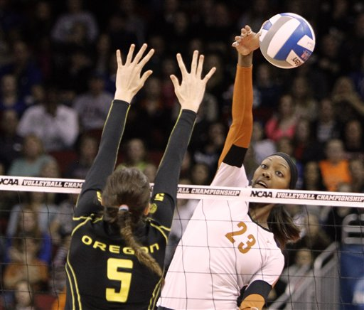<p>Texas junior Bailey Webster (23) directs the spike around the block attempt by Oregon's Canace Finley (5) during the finals of the NCAA college women's volleyball tournament in Louisville, Ky., Saturday, Dec. 15, 2012. (AP Photo/Garry Jones)</p>