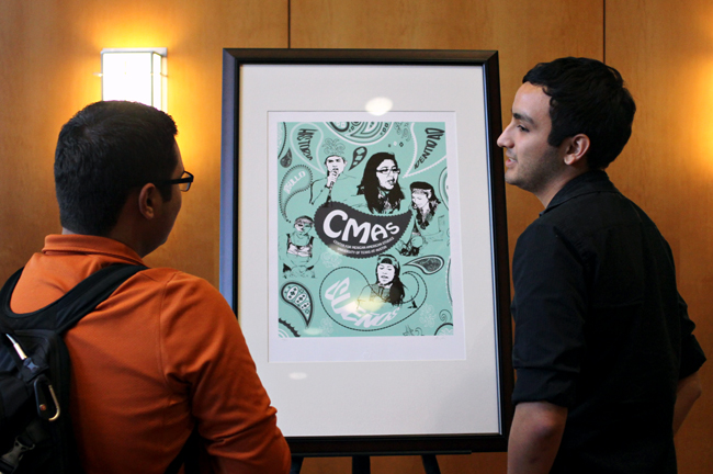 <p>Sociology junior Jonathan Cortez speaks with sociology senior Apolinar Perez about Perez's poster at the Center for Mexican American Studies Poster Art Reception Thursday afternoon.</p>