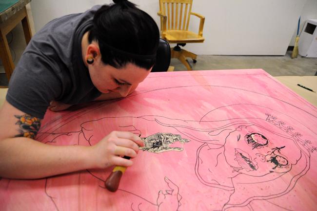<p>Senior studio art major Noelle Bilodean renders a relief print in the UT Art Building Saturday afternoon.</p>