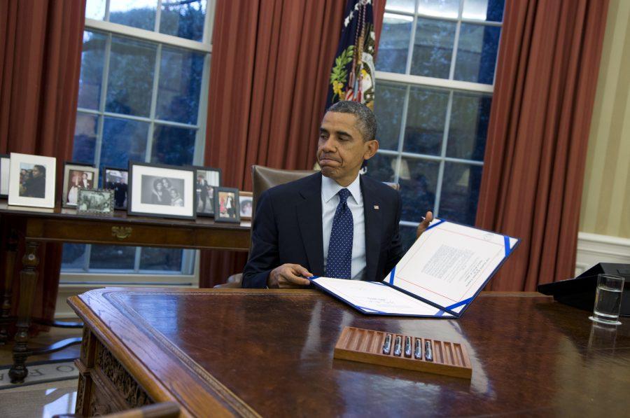 Obama looks at a folder on his desk.
