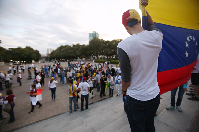 <p>Texas State graduate Alejandro Fernandez holds up a Venezuelan flag during a rally in the Main Mall on Saturday afternoon.</p>