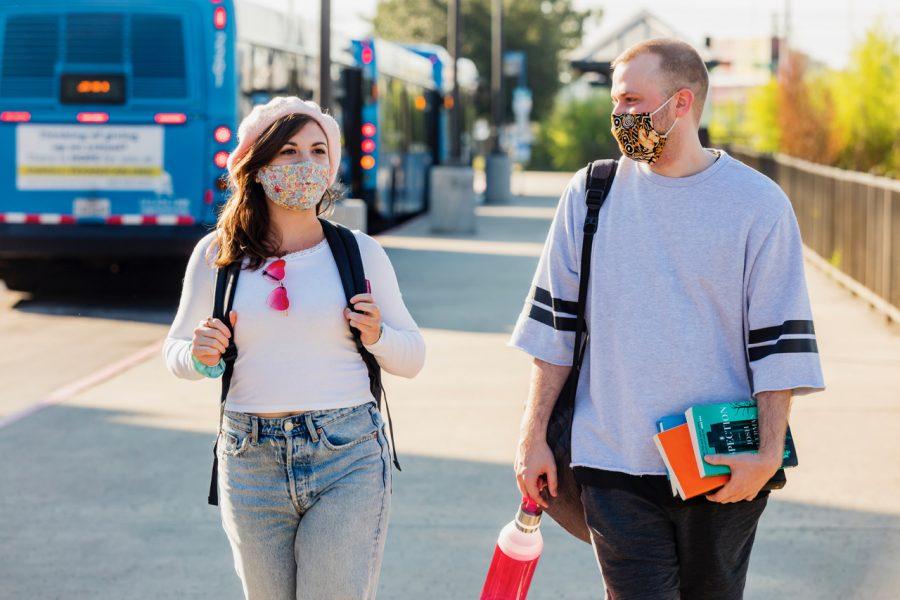 Two+people+walking+in+front+of+CapMetro+Capital+Metro+Austin+Texas+transit+bus+at+UT+Austin